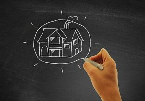 hand-drawing-a-house-on-blackboard-real-estate-and-housing-con-300x209